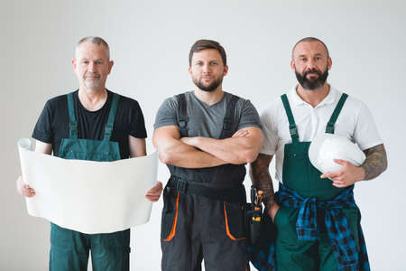 Group of three builders preparing for remodeling of the apartment Standard-Bild