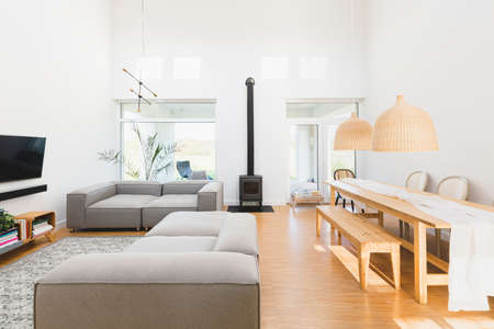 Open space living and dining room interior with flat tv, gray sofa and wooden table with trendy chairs