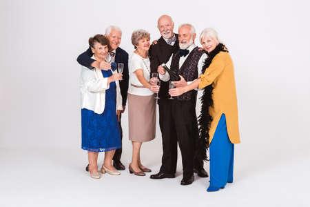 Group of elderly happy friends opening a bottle of champagne Standard-Bild