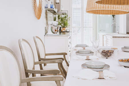 Stylish plates on white table in elegant bright living room interior with wooden chairs