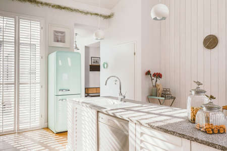 Bright kitchen interior with modern white furniture, pastel mint fridge and big floor to ceiling window
