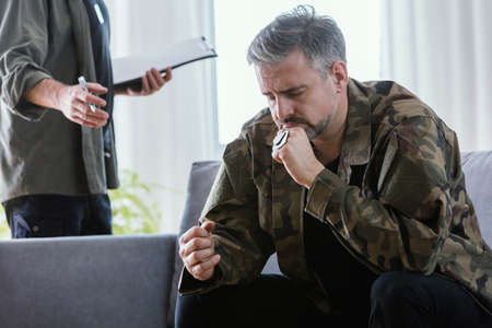 Middle aged man treating his trauma after war at psychotherapist