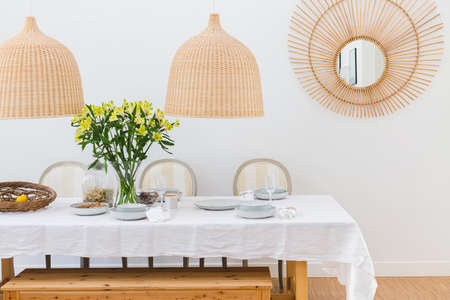 Gray plates, vine glasses and yellow flowers in vase in trendy dining room interior with wicker chandeliers