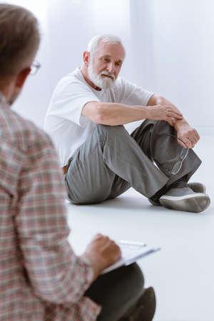 Sad gray senior man sitting on the floor during group psychotherapy for men Standard-Bild