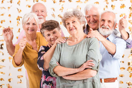 Happy group of senior friends looking through a curtain of golden decorations Standard-Bild