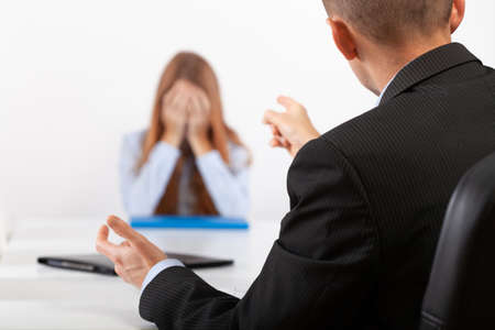 Depressed young woman during a conversation with the boss who points out her mistakes Standard-Bild