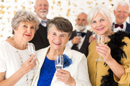Three elegant older friends make a toast with champagne during the birthday party