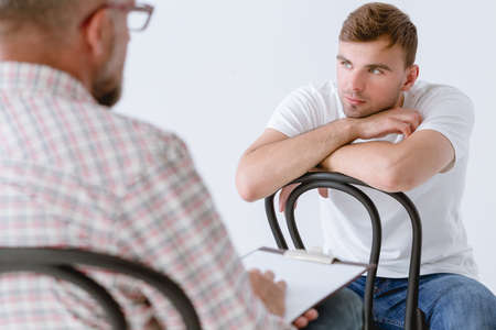 Young man and professional counselor during psychotherapy for people with ptsd Standard-Bild