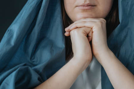 Close-up of Mother Mary wearing blue robes praying to the god