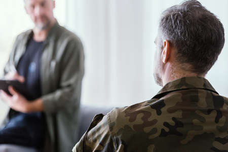 Man in army uniform trating his fears during psychological session Standard-Bild