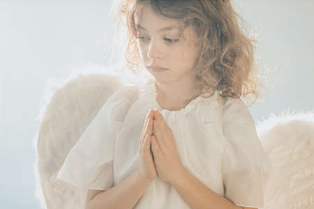 Picture of little angel boy praying with his hands together
