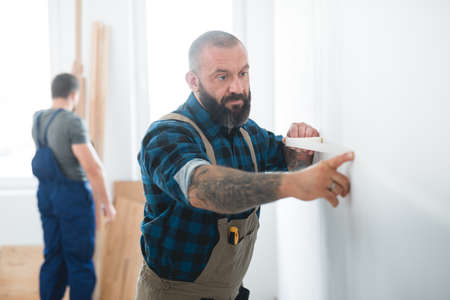 Professional builder puts a tape on an empty wall before painting it Standard-Bild