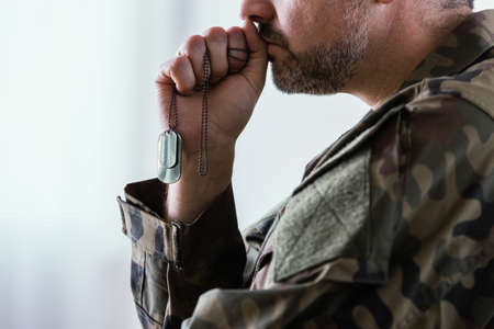 Soldier in uniform holding his dog tag and thinking about the war