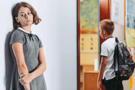 Lonely sad girl standing alone on a school corridor during break Stock fotó