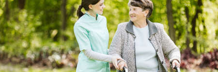 Senior disabled woman with caregiver in the garden of the nursing home Stockfoto