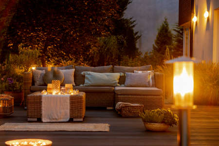 Warm summer night in the garden with trendy furniture, lights, lanterns and candles Stockfoto