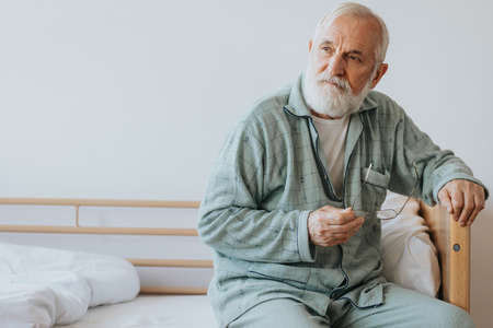 elderly man with gray beard and hair sits in pajamas on the bed with glasses in hand