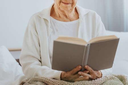 Senior woman reading book in nursing home Archivio Fotografico