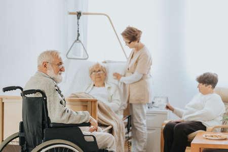 Senior doctor in a beige uniform talks to an elderly patient during a walk around hospital