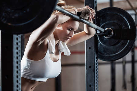 Close-up of young female bodybuilder taking break after training at crossfit center Imagens