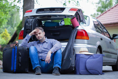 Handsome man sitting on the road next to car with open trunk Foto de archivo