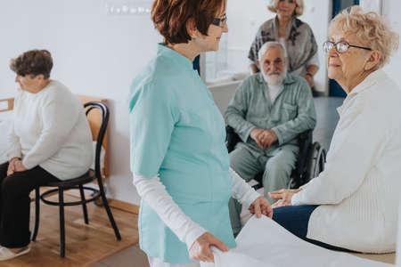 Senior patients and nurse in local nursing home