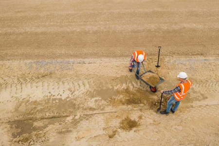 Top view of two road construction workers in orange vests and protective helmets in the middle on the field