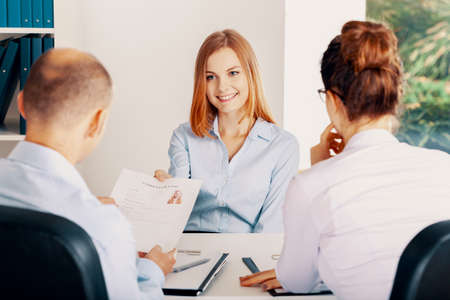 Smiling young woman during interview in small start-up