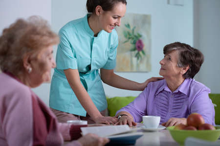 Senior patient of professional nursing home and helpful young nurse