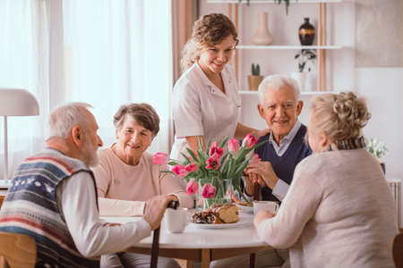 A group of senior people sitting by the table in a nursing home Stok Fotoğraf
