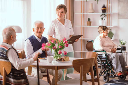 A group of senior people sitting by the table in a nursing home