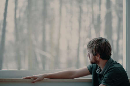 Thoughtful young man sitting on windowsill looking through the window