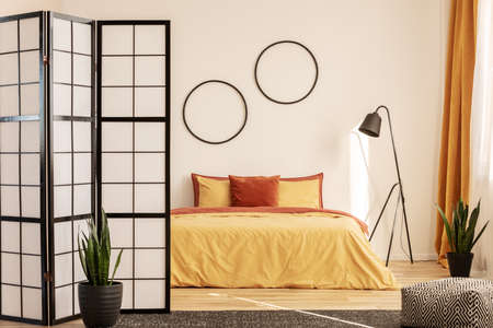 Stylish bedroom design with orange and yellow colors in modern apartment