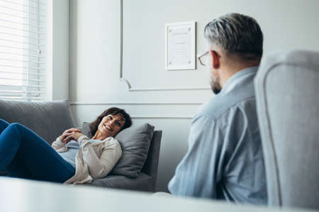 Happy housewife lies on the gray couch in front of counselor