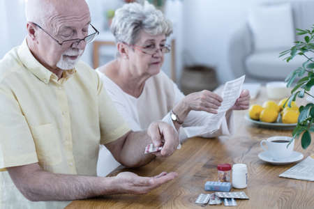 Husband taking his medicines and wife reading a brochure