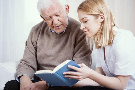 Young blonde volunteer reading book to senior man in nursing home Archivio Fotografico
