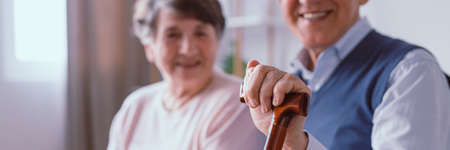 Older man with walking stick sitting in nursing home with his wife