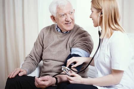 Senior gray man with supporting measuring blood pressure Archivio Fotografico