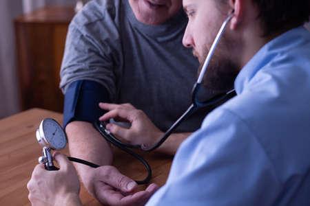 Closeup of young male nurse measuring blood pressure of senior man
