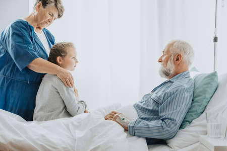 Young girl and her grandmother visiting her sick grandfather in the hospital Stok Fotoğraf