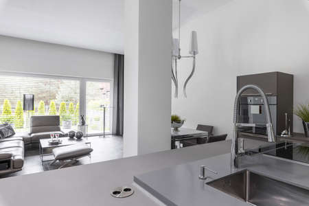Elegant kitchen with dining room table and gray design in fashionable house