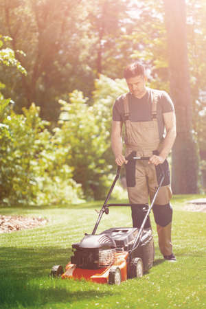 Young handsome gardener waring brown overall and mowing the grass Stok Fotoğraf
