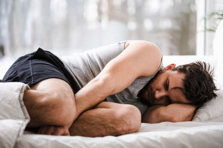 Young man curling up on a bed after sleepless night