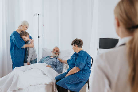 Terminally sick older man and his family staying by his bed in the hospital