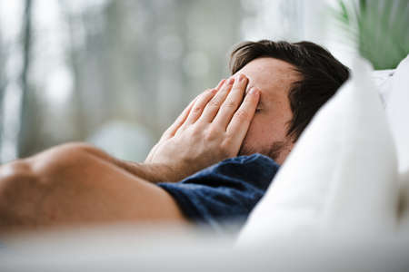 Worried young man with insomnia in bed trying to fall asleep in the morning