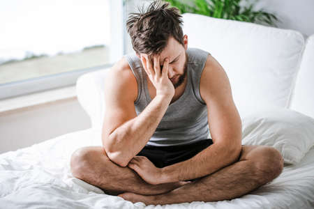 Tired young man sitting on a bed after night without sleep