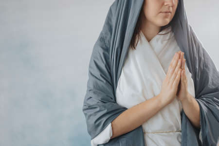 Mother Mary in white and blue robes praying to the God