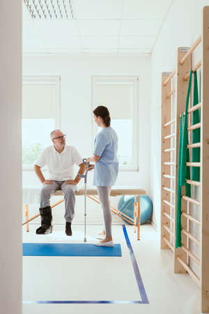Elderly man sitting on a physiotherapy table during rehabilitation Stok Fotoğraf