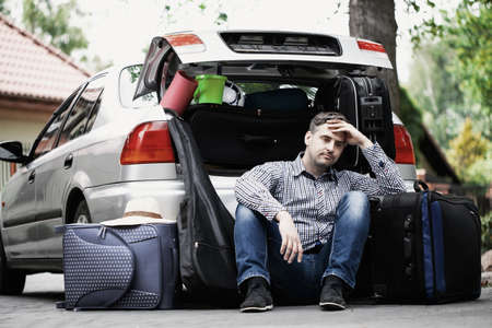 Handsome man sitting on the road next to car with open trunk