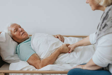 Senior woman holding her sick husband's hand